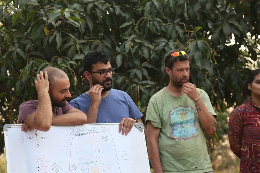 Участници в курса по пермакултура изслушват обратна връзка върху проекта си.