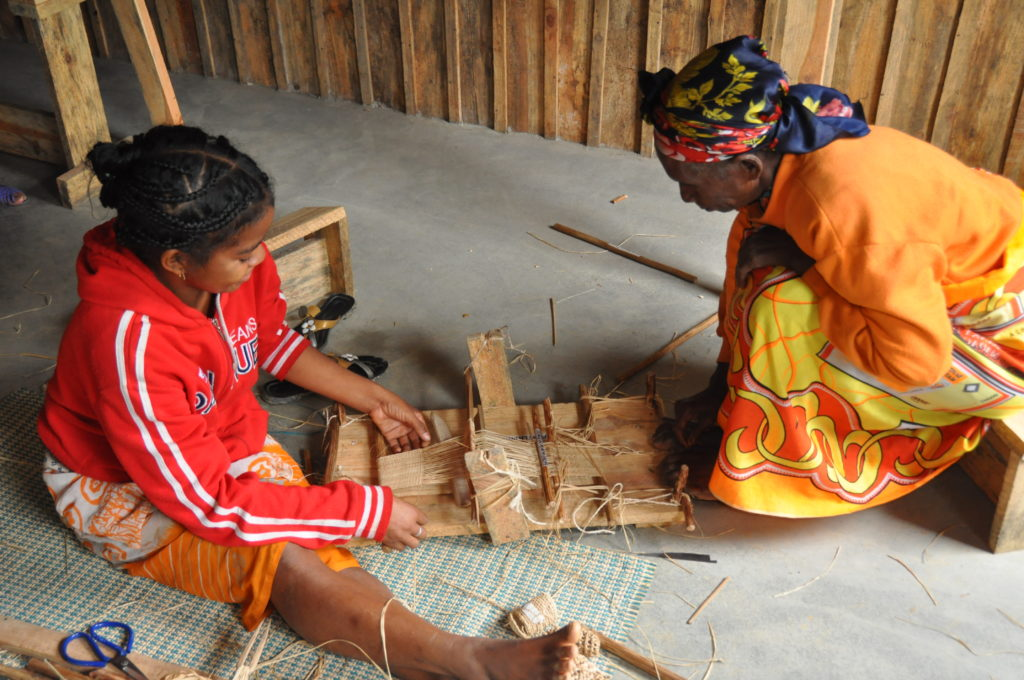 A woman and weaving girl at a loom in Madagascar.